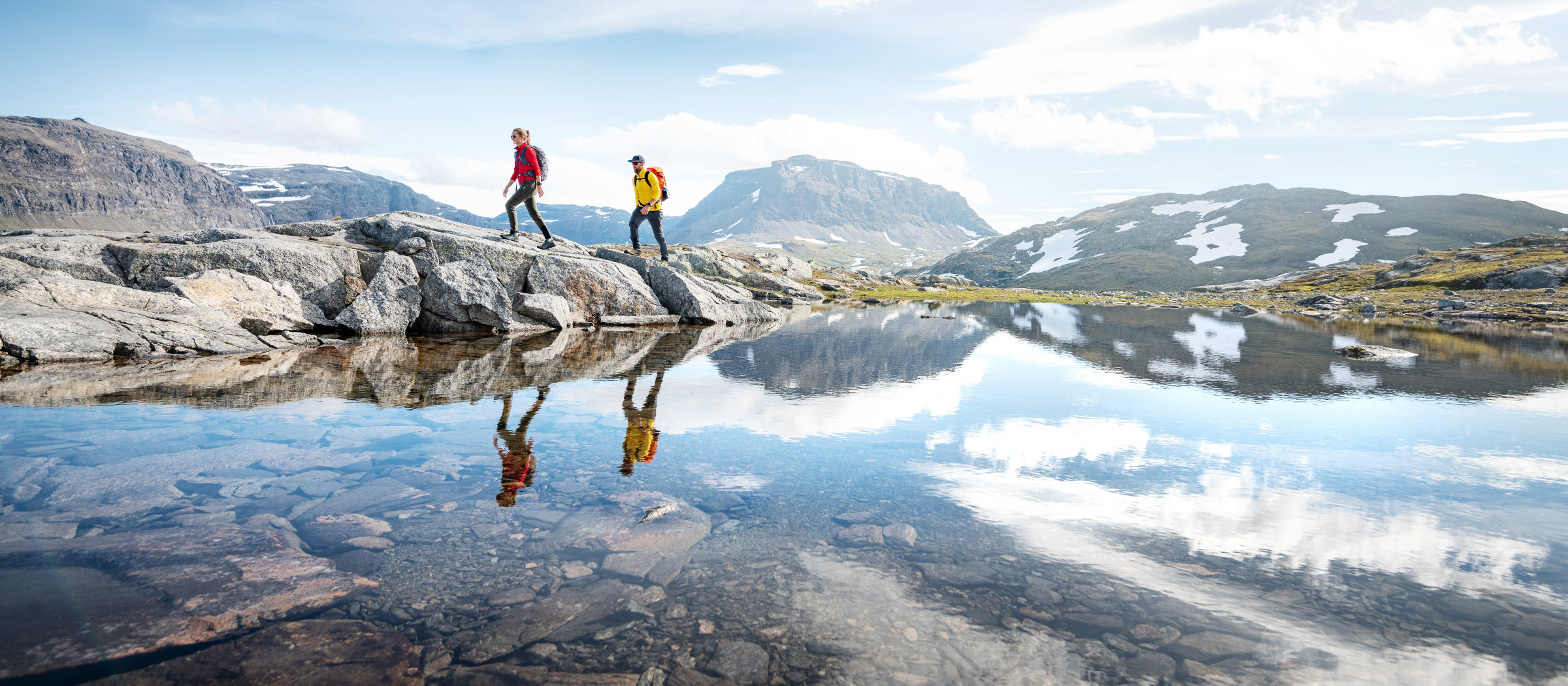 Two hikers are exploring a valley in Björkliden, surrounded by mountains. Wearing the Stellar EQ Ultralight Shell jackets.